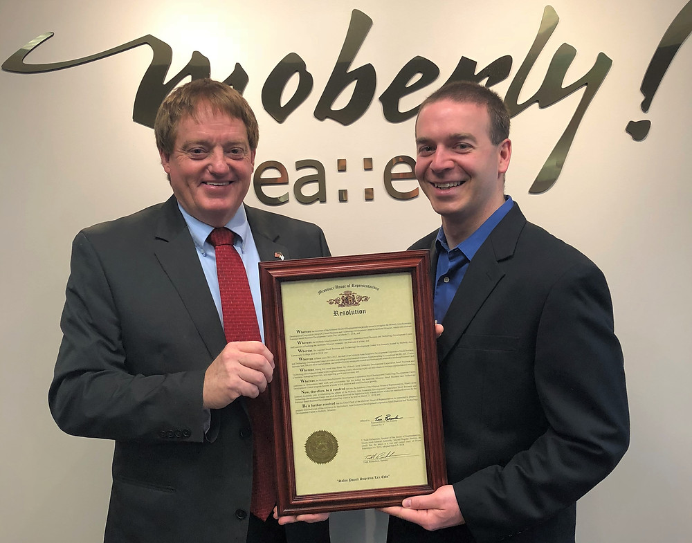 Rep. Tim Remole (left) presents Ryan Eidson, Entrepreneurship Specialist, with a House Resolution at the MAEDC office in downtown Moberly.