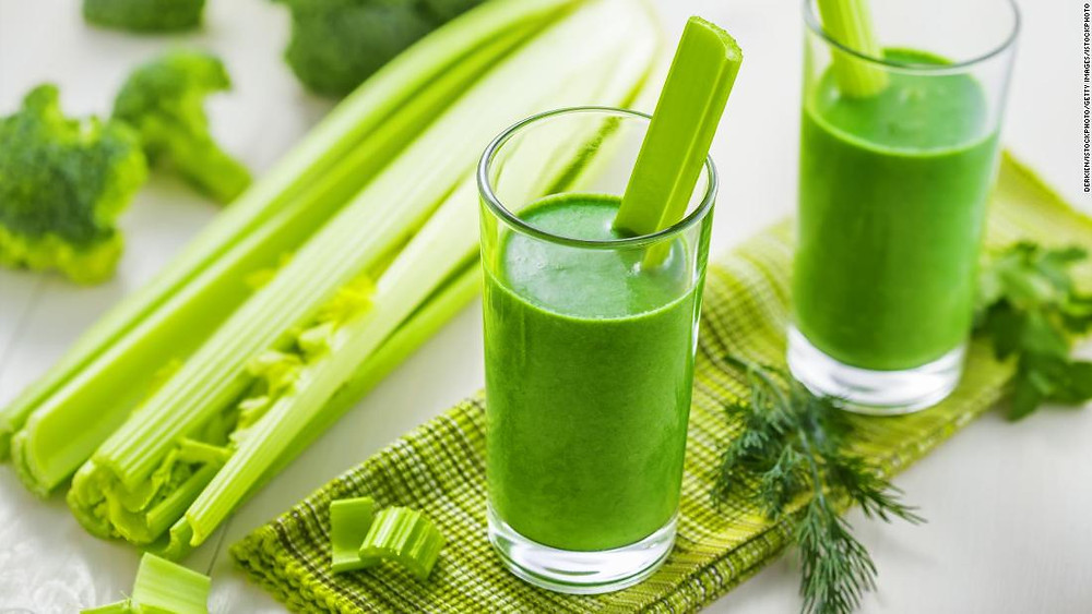 Two tall glasses of green celery juice beside whole stalks of celery.
