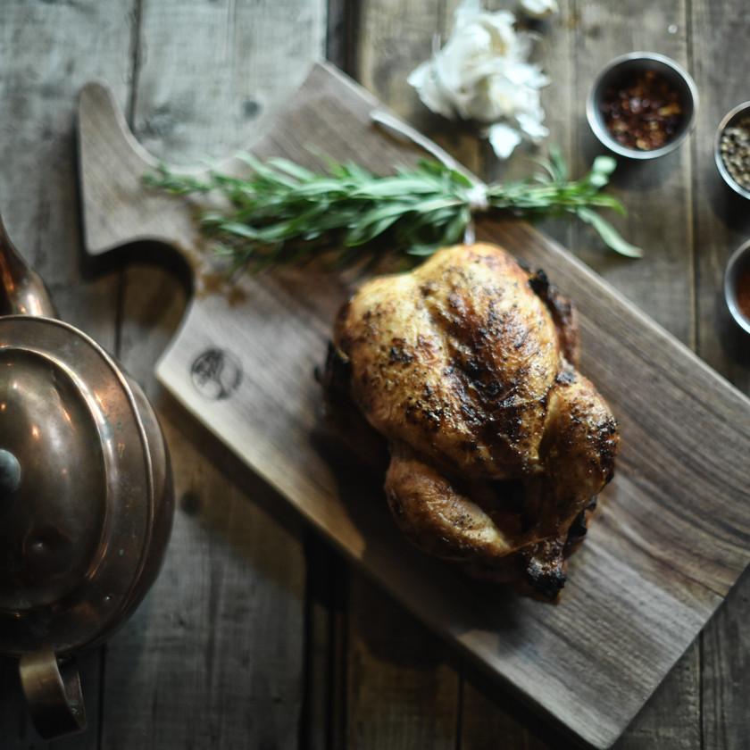 Roasted chicken on a chopping board with rosemary and spices around it.