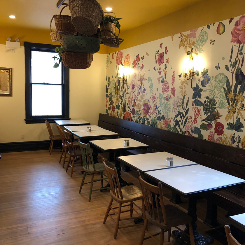 Small dining room in a restaurant. Brightly coloured flower wallpaper on the wall.