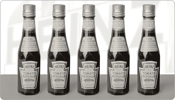 Heinz ketchup bottles from 1948 lined up. Photo in black and white.