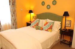 Deep yellow room, white bedding