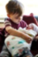 Big brother holding a newborn baby.