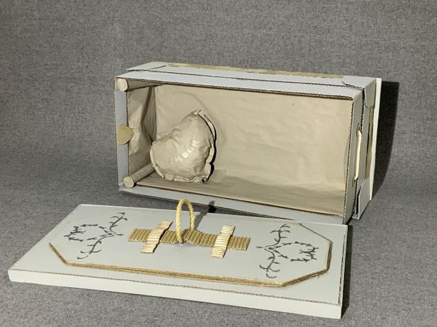 cercueil avec couvercle ouvert affichant un oreiller en forme de coeur