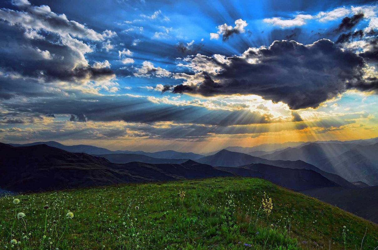 soleil brille à travers les nuages au sommet des collines