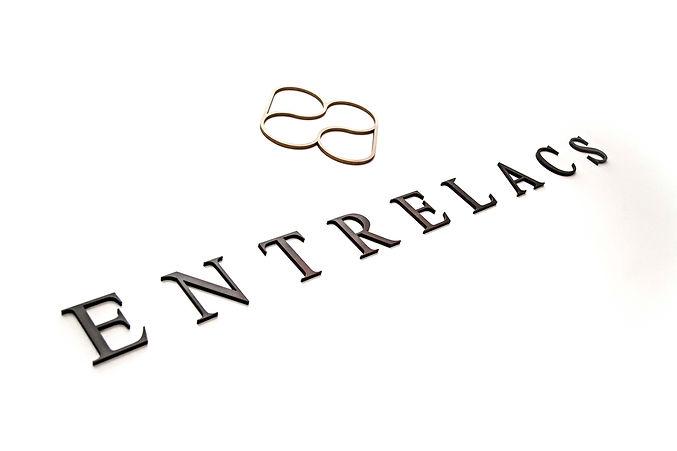 """Camille Gentil, graphiste et photographe, a créé le logo """"Entrelacs"""". Cette entreprise est spécialisée dans la création de mobilier et de luminaire en bronze. Le logo est le premier symbole  représentatif de la marque, indispensable à l'identité visuelle."""