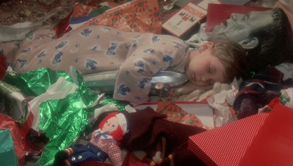 The youngest son Randy falls asleep among his gifts.