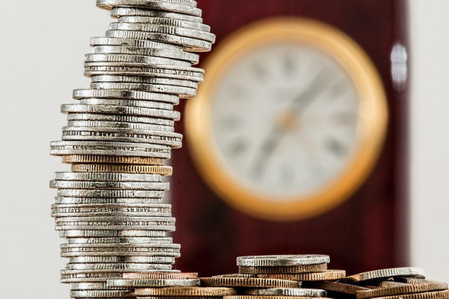 Stack of quarters beside a blurry clock