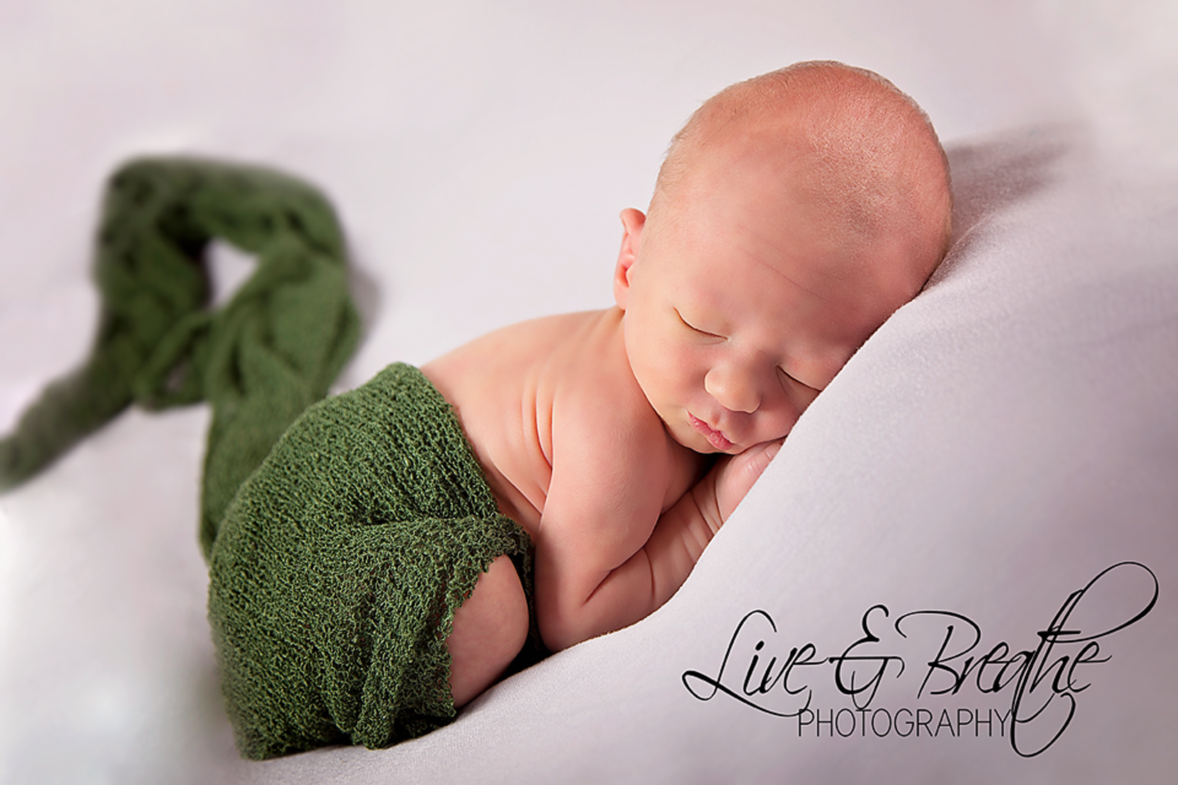 Newborn curled up with green wrap