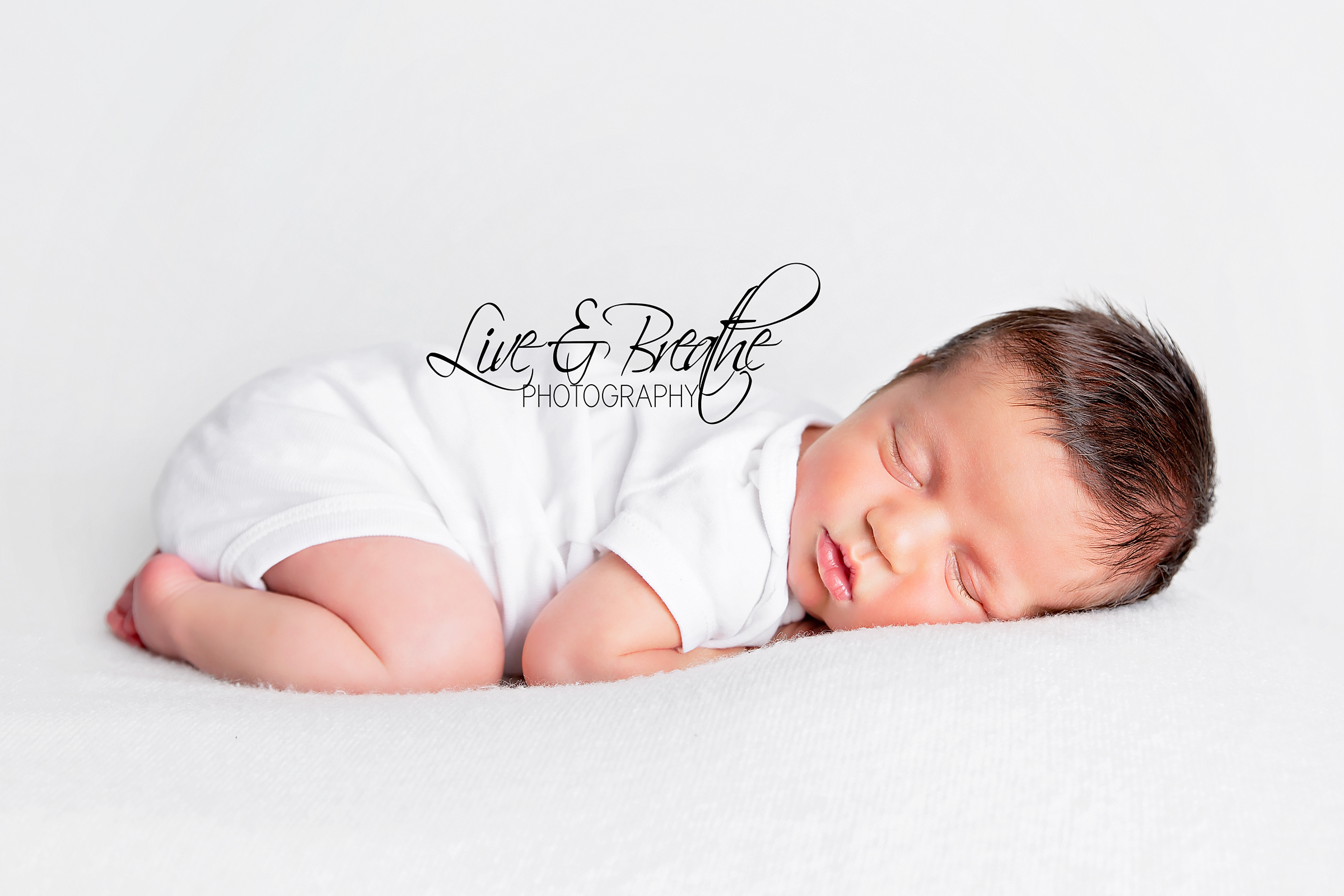 newborn boy curled up