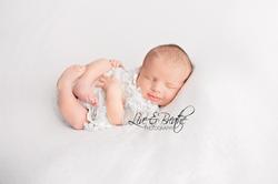 newborn girl curled up
