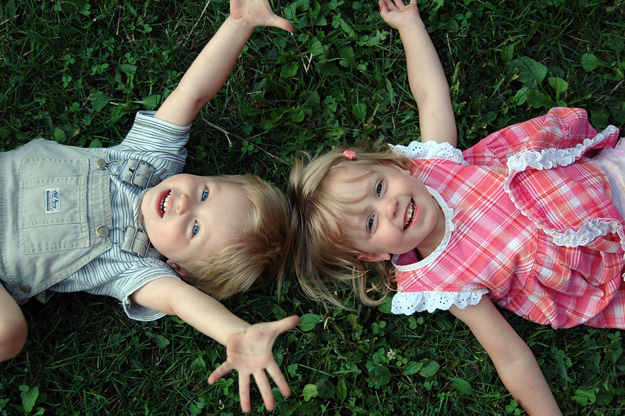 Boy and girl twin toddlers laying on the grass with their arms wide open.