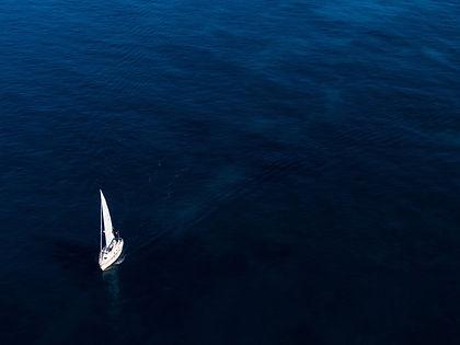 aerial-shot-small-white-boat-sailing-oce