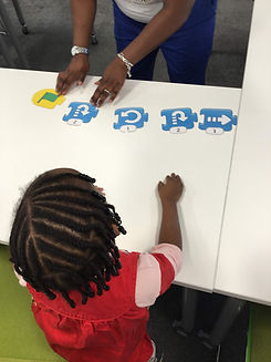Beautiful black girl with bead in her hair taking part in an unplugged coding activity in Wimbledon.