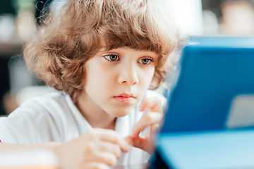 Curly haired child-using a First Class Coders for computer programming.