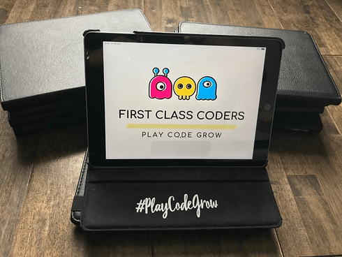 Picture of customised First Class Coders Tablet with #PlayCodeGrow slogan on them.