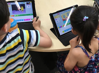 Asian boy and girl, children coding using their First Class Coders tablets in Wimbledon, London.