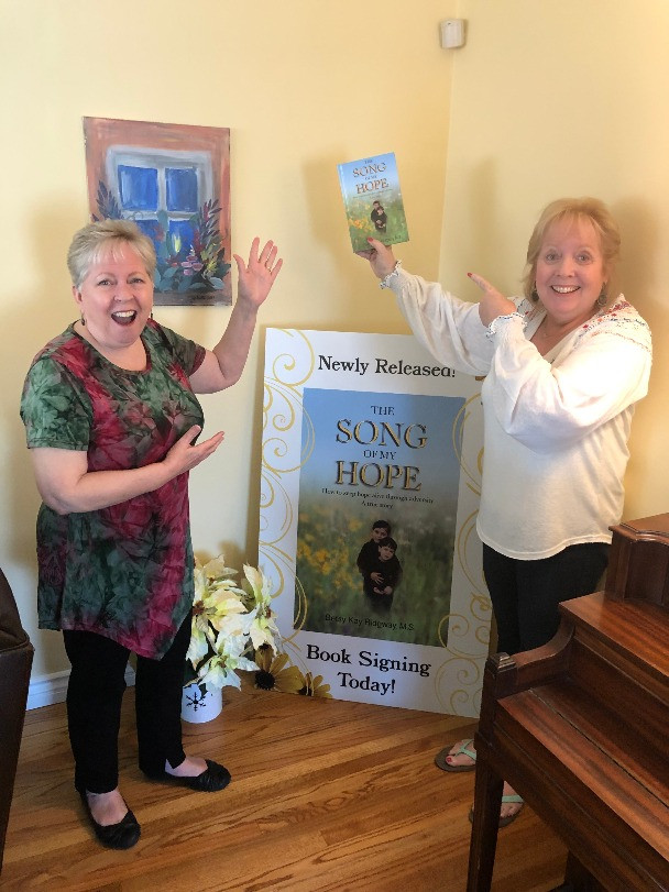 Betsy Ridgway and her sister holding newly released book