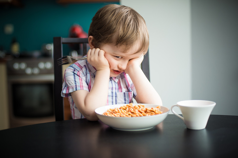 Upset little boy sitting in front of a bowl of cereal