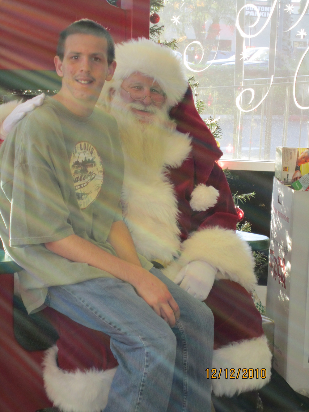 Teenage boy sitting on Santa's lap
