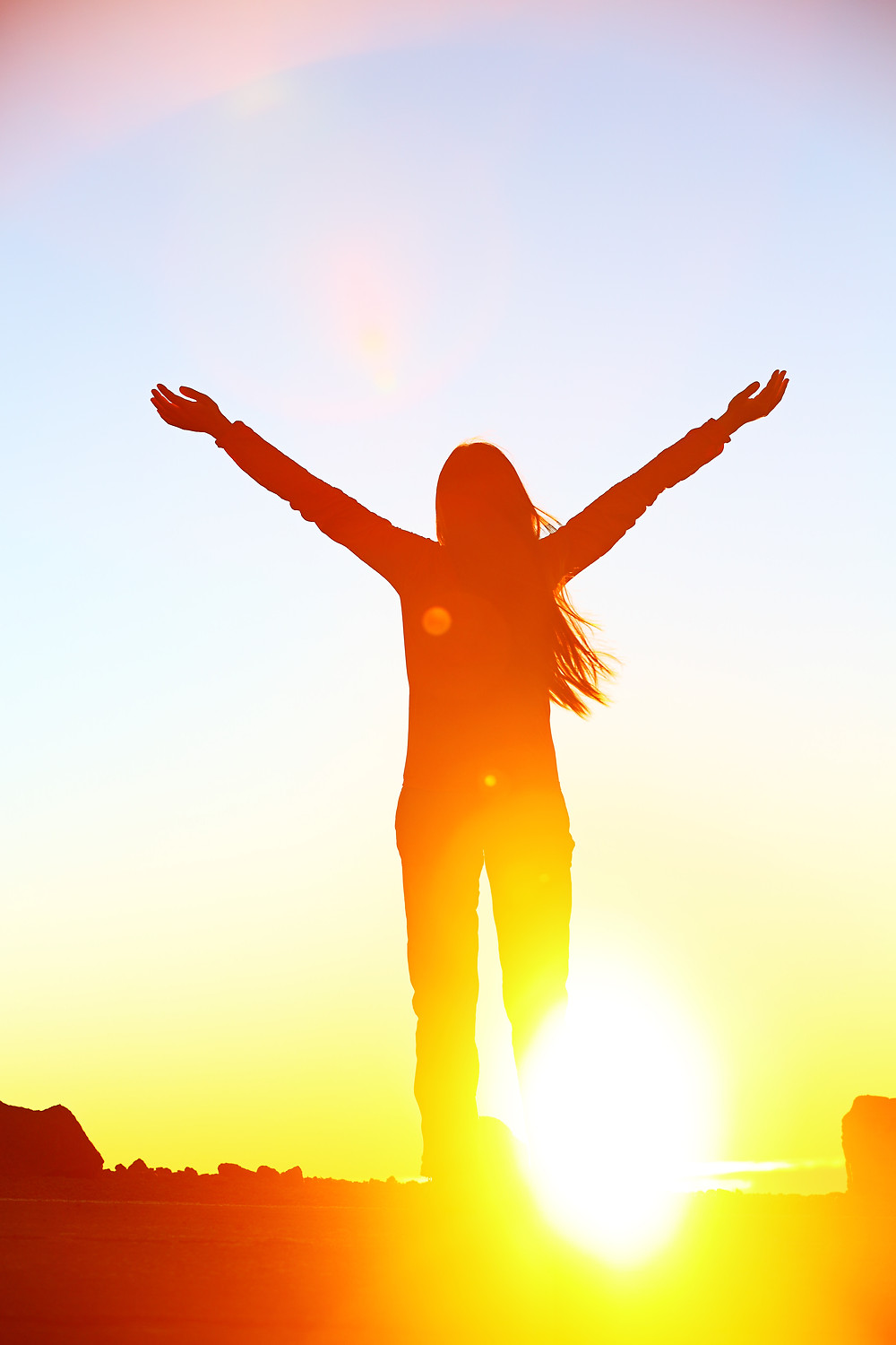 Woman with arms outstretched toward sunrise