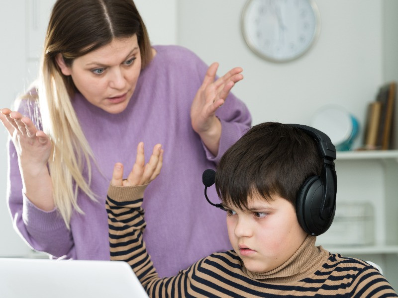 Mom ordering rebellious boy at computer