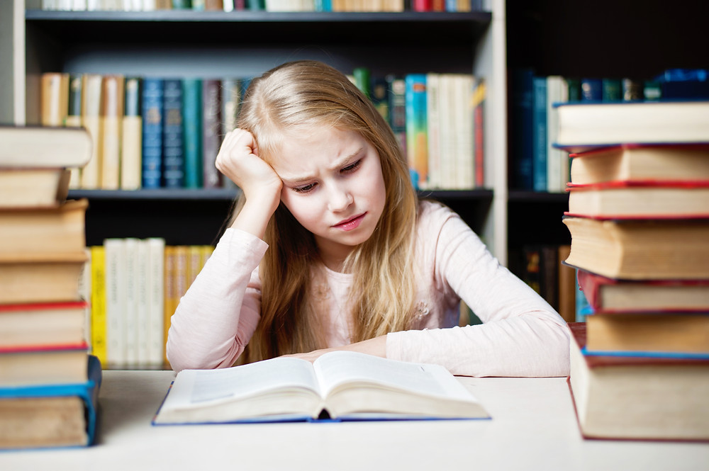 Girl in library looking frustrated as she reads a book