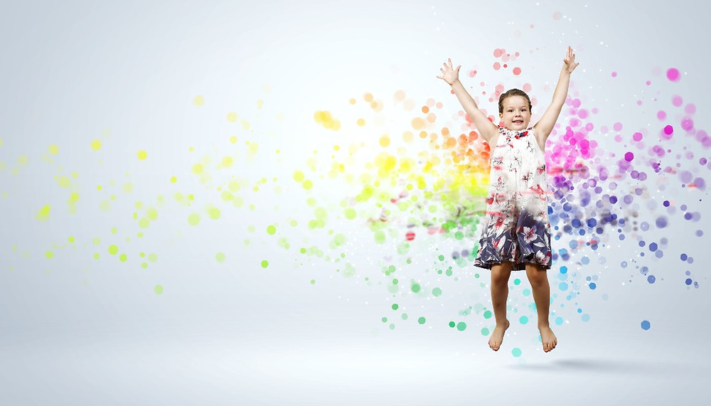 Child jumping surrounded with colorful blobs