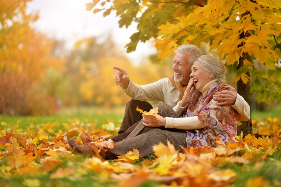 Happy older couple sitting in fall leaves.