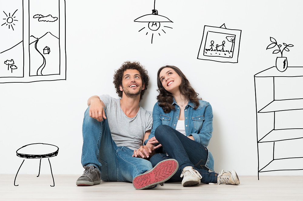 Couple sitting on floor imagining their future represented with drawings