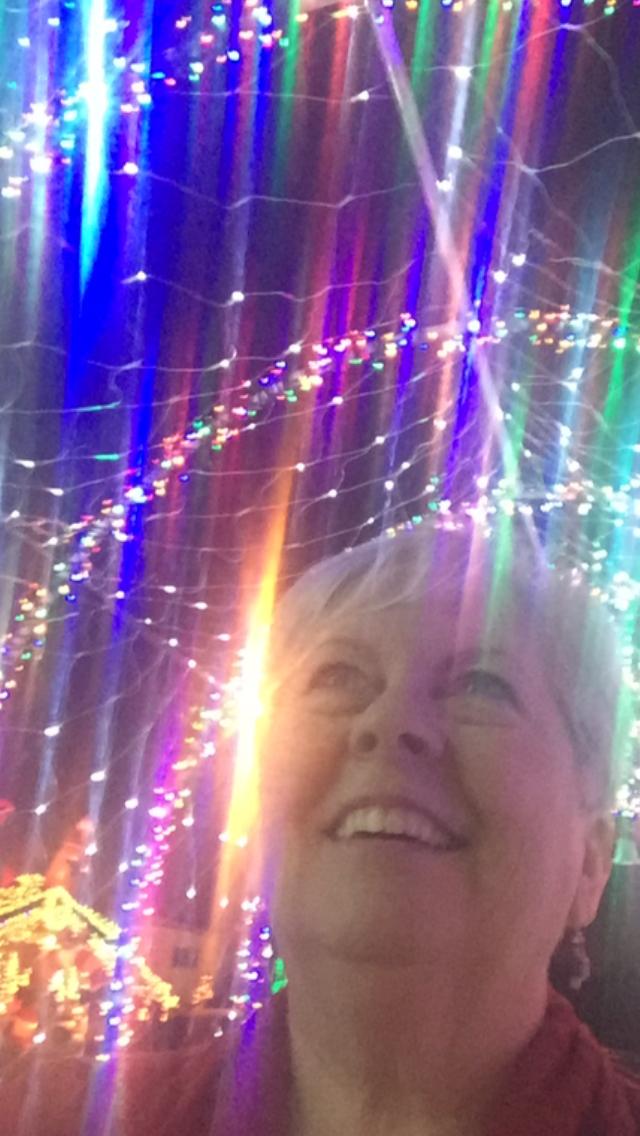 Woman looking up at Christmas lights
