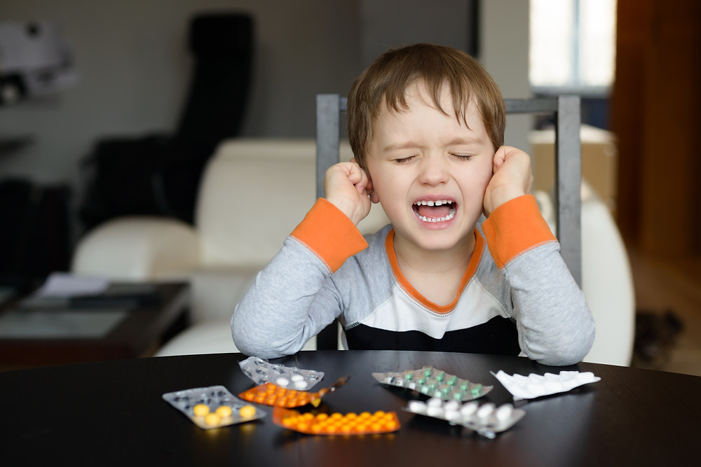 Child crying by table of medication packets