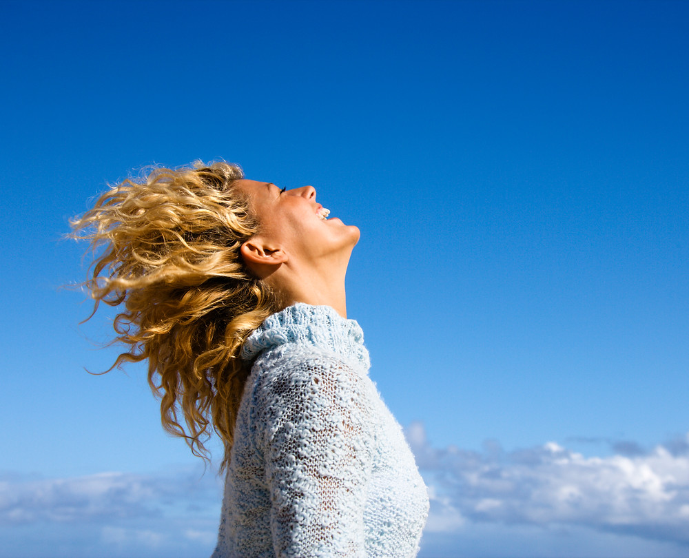 Joyful woman with wind blowing through hair
