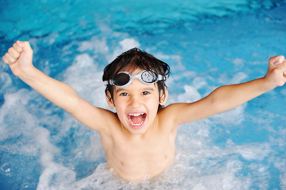 Boy, arms outstretched in pool