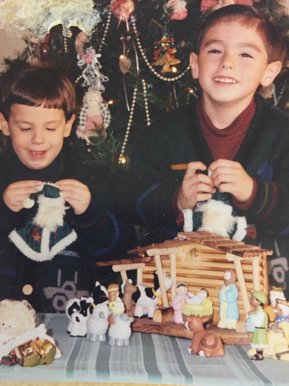 Two young boys playing with a manger scene