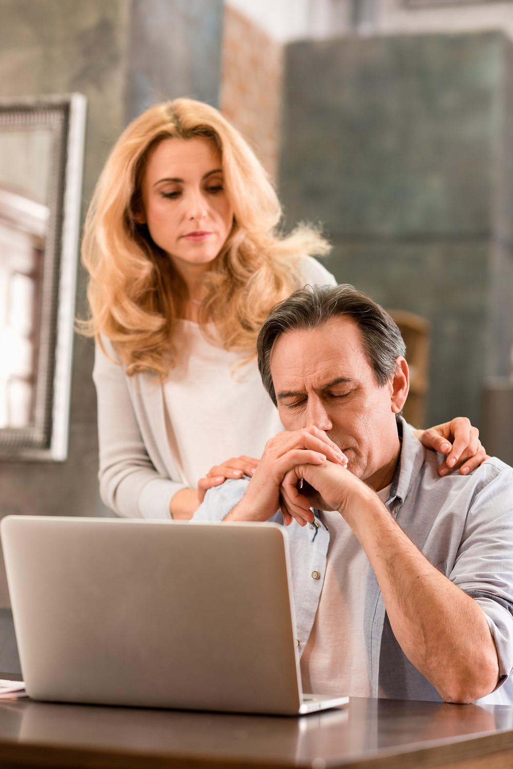 Anxious man in front of computer with woman behind trying to comfort him
