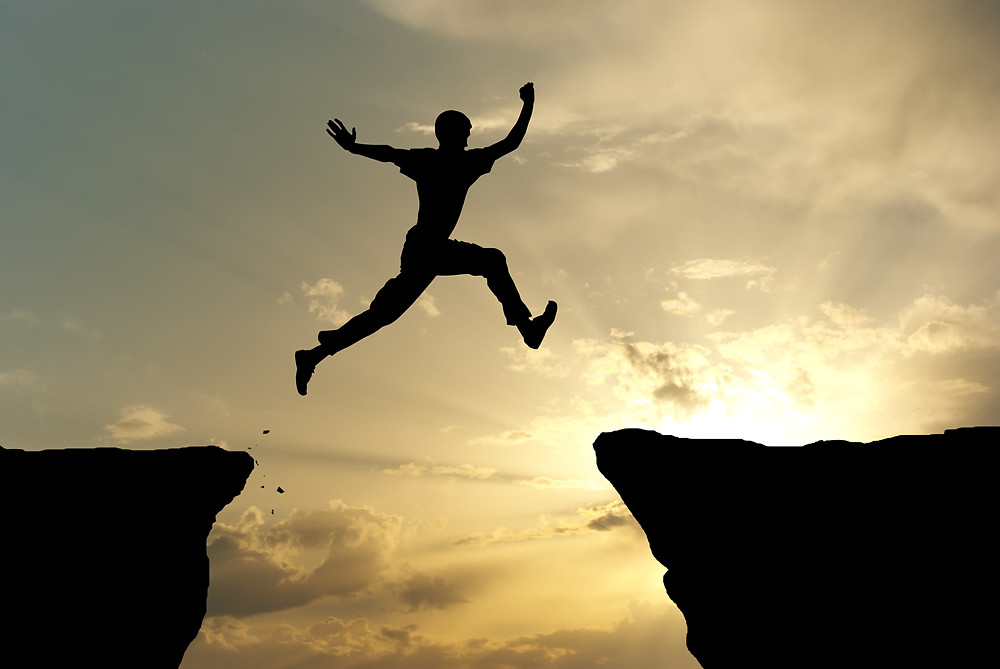 Man jumping over a large cliff