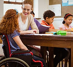 A teacher sits at a table with a group of young students, one of which is a girl in a wheelchair.