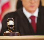 A judge in a courtroom bangs his gavel.