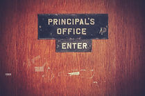 """Photo of a door with a sign reading """"Principal's Office - Enter""""."""