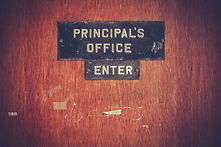 "Photo of a door with a sign reading ""Principal's Office - Enter""."