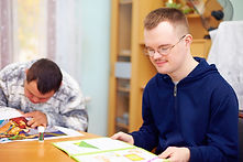 Two students work at a table in a special education classroom.