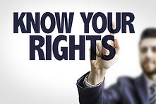 "A man in a suit points to large word that read ""KNOW YOUR RIGHTS""."