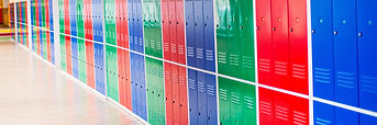 A school hallway with a long row of lockers painted blue, red, and green.