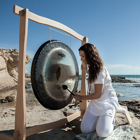 Esther tocando el gong en la playa