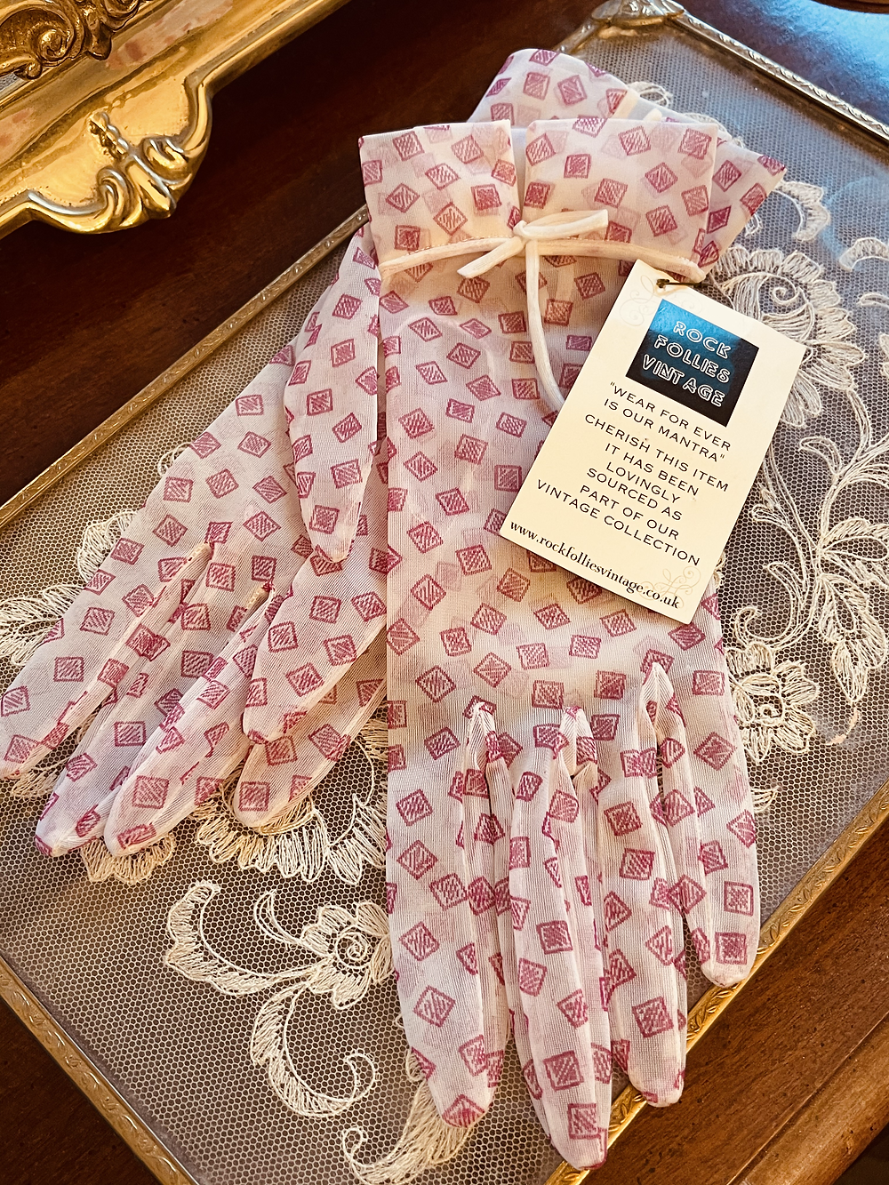 Sheer cream gloves with tiny pink pattern and bow trim