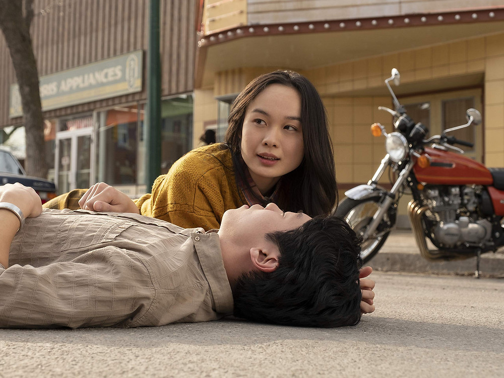 A woman and a man lie down in the middle of the road, behind them stands a motorbike parked outside a cinema
