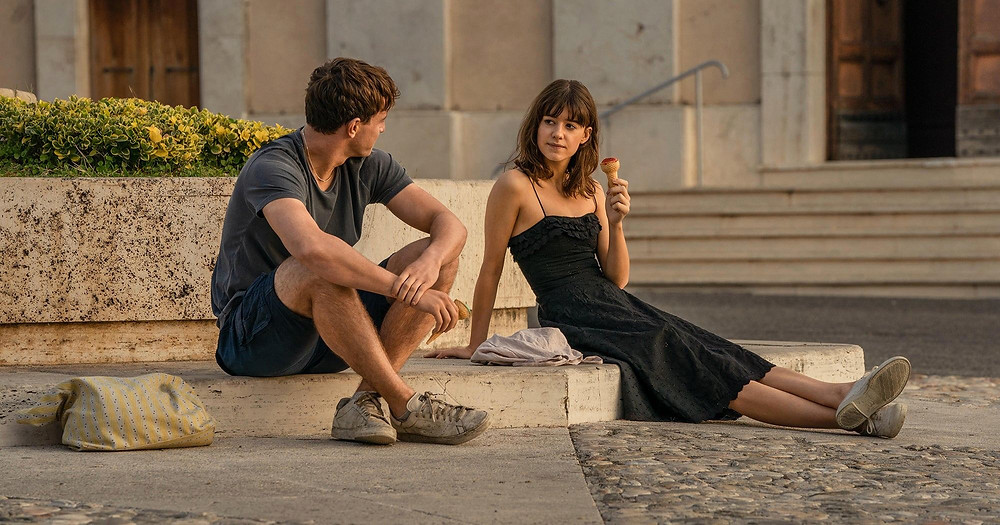A man and a woman sit on the curb in a small town in Italy. The glow of the sunset lights the scene while the pair look at each other. The woman eats an ice cream.