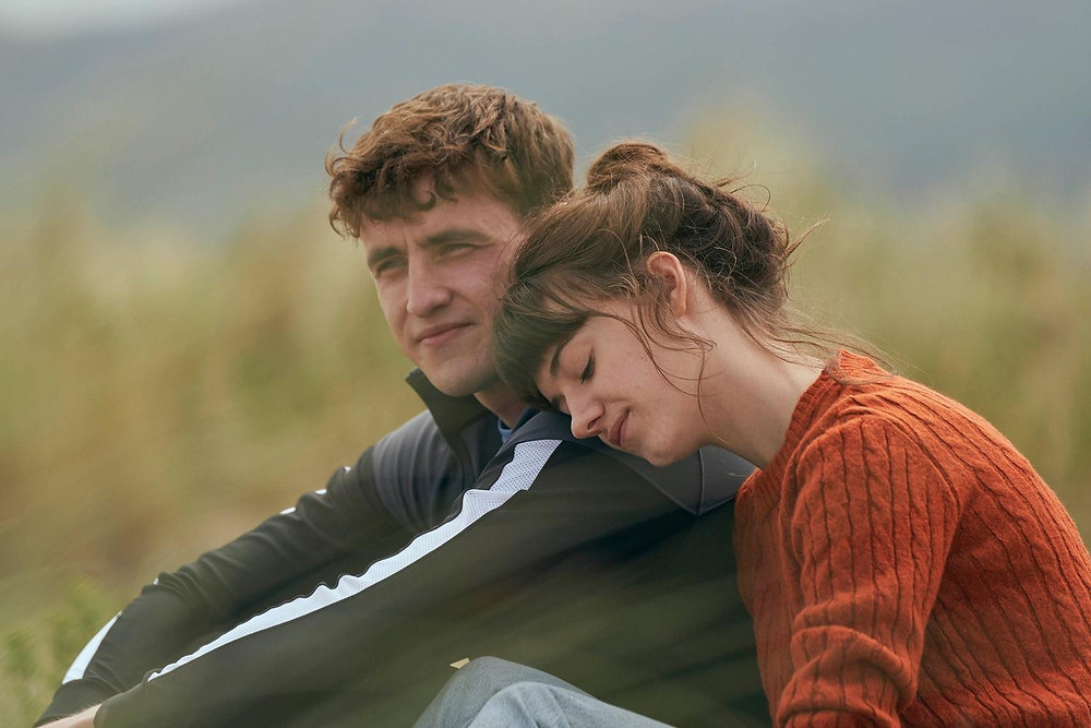 A man and a woman sit on the grassy ridge of a beach. The man stares out to sea as the woman leans her head on his shoulder.