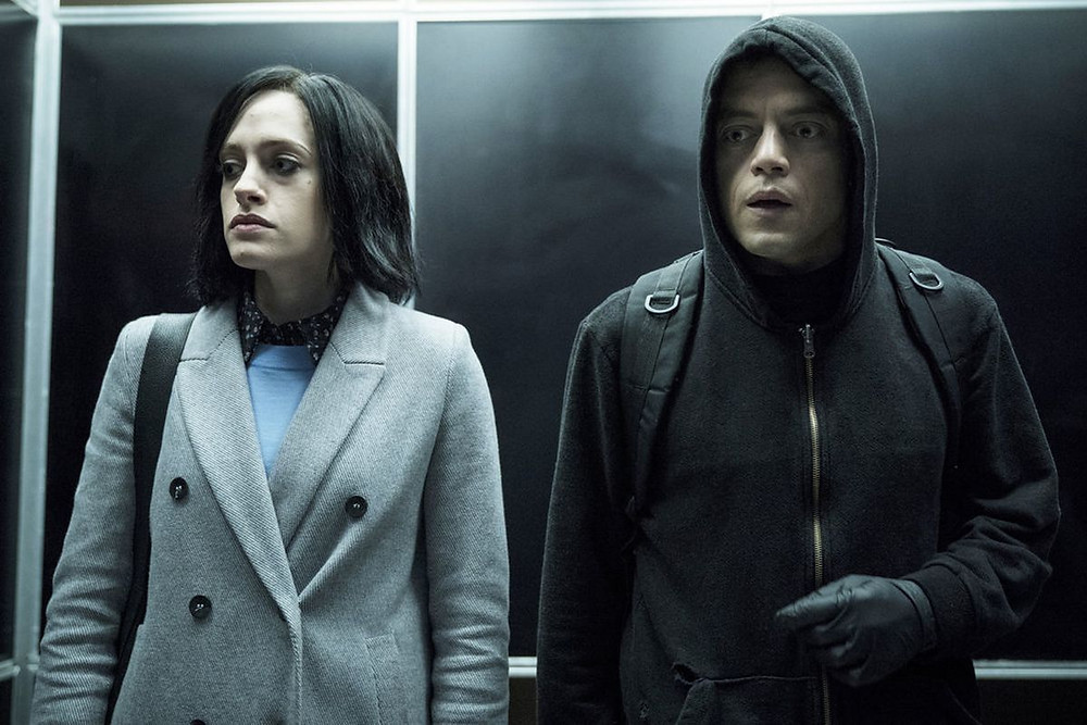 A woman and a man stand in the lift, they both look stressed, the man has his hood up and the woman is wearing a wig.